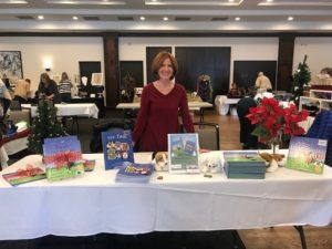 Pat Postek showcasing her books at a book fair